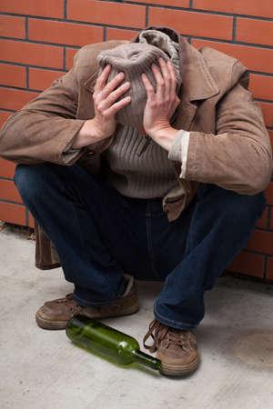 avergonzado: Alcholic deprimida que se sienta en el suelo con una botella vacía.