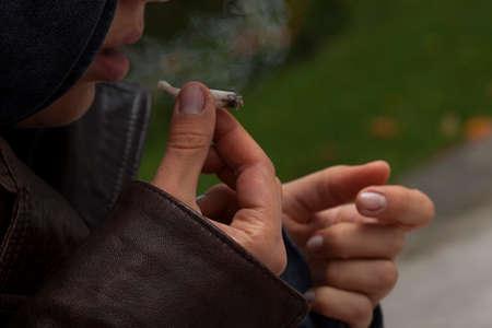 chica fumando: Chica joven con chaqueta de cuero fumando un porro