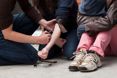 drug use: Man injecting heroin to young girl in a basement. Stock Photo