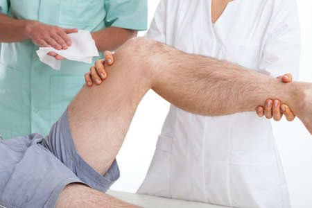 Doctor examining a patient with a painful leg photo