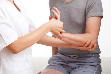 masaje deportivo: Mujer fisioterapeuta examinar y masajear la mano