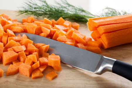 cutting vegetables: Chopped carrot with knife on the cutting board