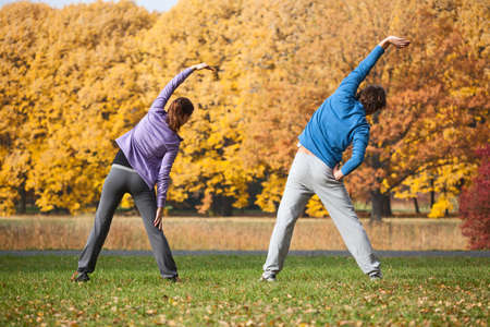 Couple doing exercises in park during autumn