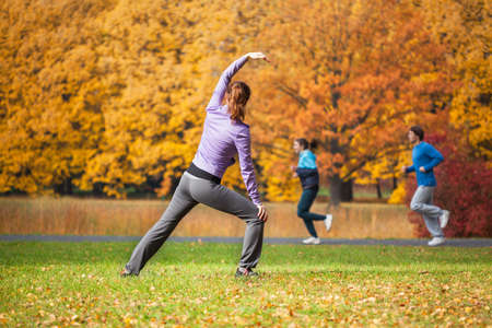 tai chi: Young woman doing yoga in the autumn park Stock Photo