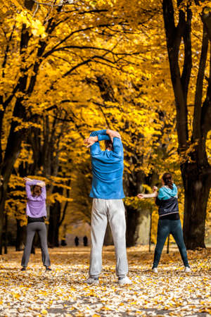 Group of people working out in park in autumn photo