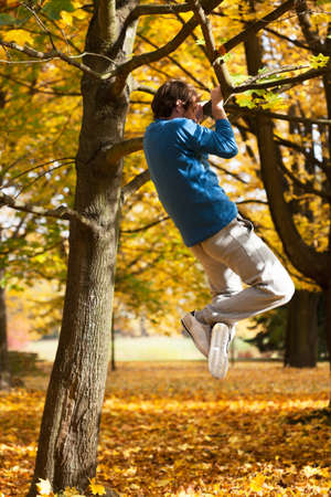 Man pulling up  himself on the tree in colourful park photo