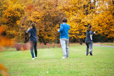 Friends practicing tai chi in autumn park photo