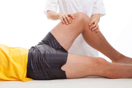 sport woman: Physiotherapist massaging and examining injured leg Stock Photo