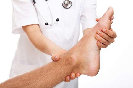 Female physician examining foot on white isolated background photo