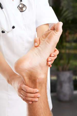 Female physiotherapist examining mans painful  and twisted ankle photo