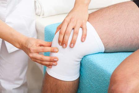 tendones: Doctor que examina la rodilla trenzado de paciente