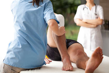 on hands and knees: Female physiotherapist helping to exercise the patient injured knee