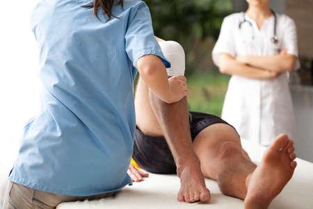 f�sica: Mujer fisioterapeuta que ayuda a ejercitar la lesi�n en la rodilla del paciente Foto de archivo