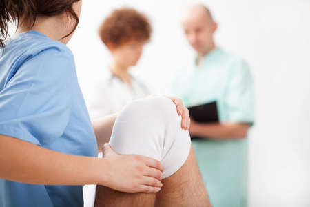 tendons: Young physiotherapist training twisted knee of patient Stock Photo