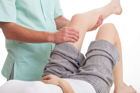 ligaments: Physiotherapist dressed in green uniform massaging womans leg
