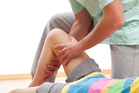 ligaments: Physiotherapist dressed in green uniform is massaging wasted leg muscles  Stock Photo