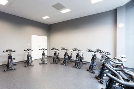 Fitness gym interior with a stationary bicycles photo