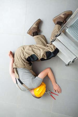 hombre cayendo: Trabajador acostado en el piso gris cerca inconsciente escalera