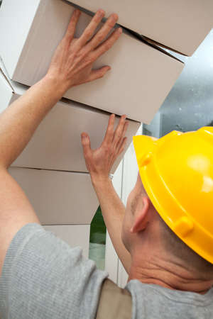 bad accident: White and heavy boxes falling on worker with yellow helmet Stock Photo