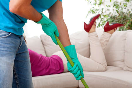 Man tidying while women laying on sofa photo