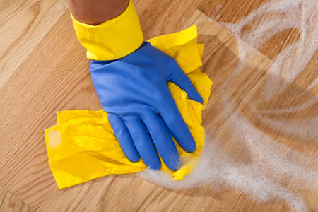 tidying up: Cleaning the wooden floor by rubber Stock Photo
