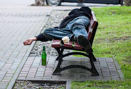 Un ivrogne sans-abri dormant sur un banc avec une bouteille Banque d'images - 23699344