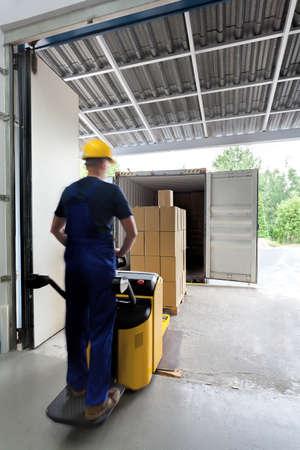 fork lift: Trabajador en uniforme en un ascensor tenedor