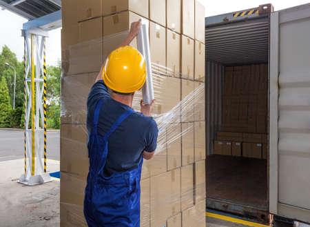 palet: Cajas de embalaje con papel de aluminio por un trabajador de almacenamiento Foto de archivo