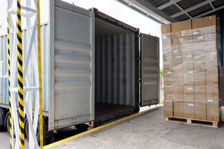 loading cargo: Forklift with carton boxes loading the truck Stock Photo