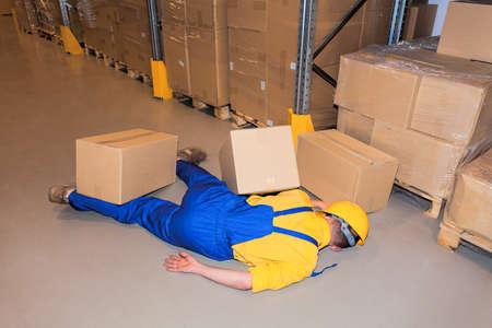 accidente trabajo: Accidente en el trabajo-trabajador bajo cajas de cartón