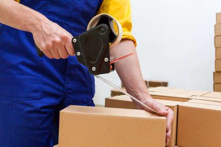dispense: Primer plano de un trabajador de las manos una caja de embalaje
