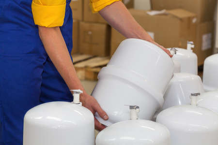water filter: Factory worker holding a pressure vessel ready to be sold
