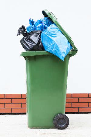rubbish bin: Blue and black rubbish sucks in a green litter bin Stock Photo