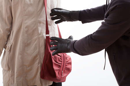 risk taking: A thief in leather gloves about to steal a red bag Stock Photo