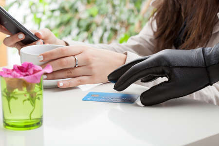 swindler: A hand with black glove striving to steal a credit card