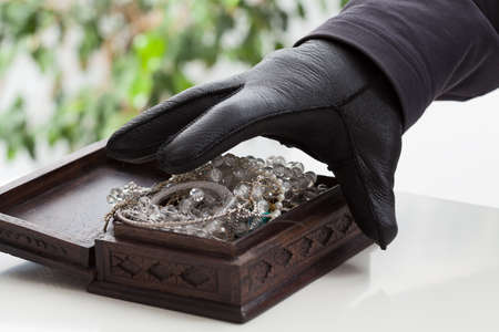 espionage: A closeup of a hand of a man about to steal a jewelery box