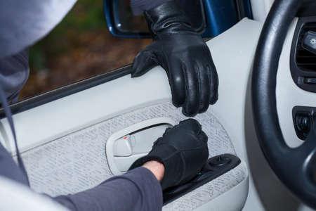 Dief draagt zwarte handschoenen breken in een auto
