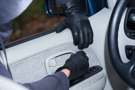 vandal: Thief wearing black gloves breaking into a car