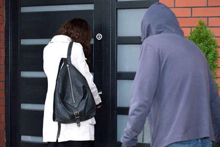 彼女の家と彼女の背後に男のフロントドアを開ける女性 写真素材