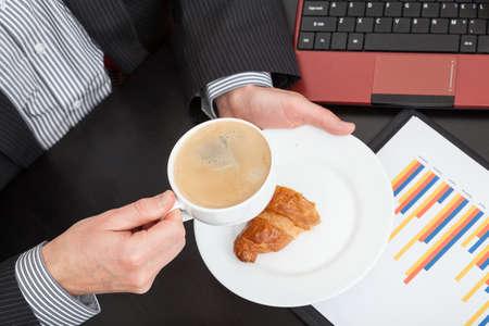 Zakenman met croissant en koffie