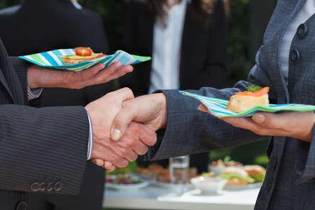 traje sastre: Apret�n de manos durante el almuerzo al aire libre Foto de archivo