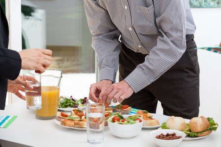 food buffet: Manager taking a small sandwich from office buffet