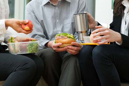 person appetizer: Young businessmen eating homemade lunch during break Stock Photo