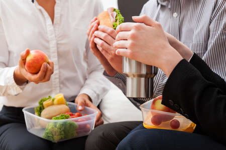 lunch box: Young managers sitting and eating meal from lunch box