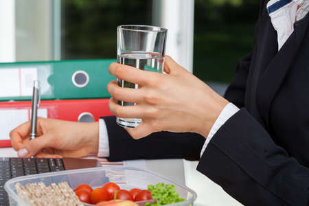 Businesswoman drinking water during work in the office photo
