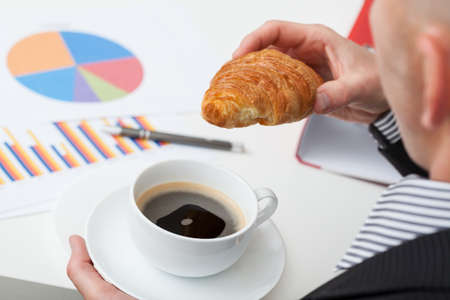 Man in suit with cup of coffee and roll above the charts photo