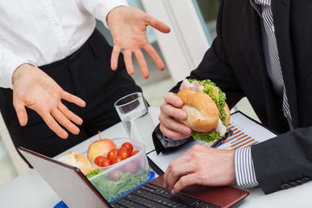 Manager push the employee to finish the meal and work  photo