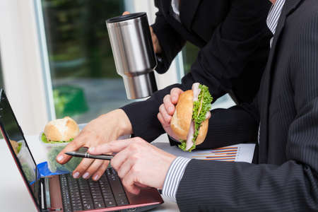 Business conversation during the lunch break with sandwiches Stock Photo - 23835738