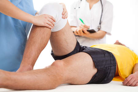 knees: Doctor checking a knee recovering in hospital Stock Photo