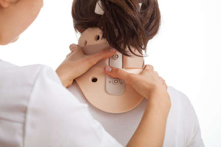 head collar: Doctor imposing a cervical collar to patient with sick neck